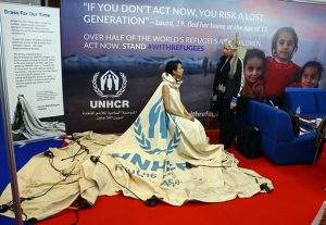 """Project ambassador of """"Dress For Our Time"""" Louise Owen models a UN tent from the Zaatari camp in Jordan that has been converted into a dress by fashion academic Helen Storey (R) at the Dubai Humanitarian Aid and Development conference and Exhibition in Dubai on March 22, 2017. / AFP PHOTO / NEZAR BALOUT"""
